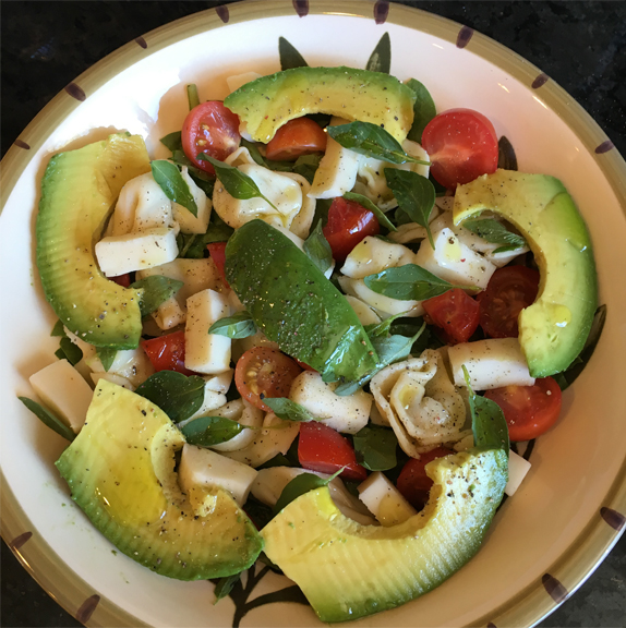 Image of caprese salad with avocado and fresh basil